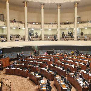 Historiallinen sähköinen äänestys eduskunnan lehtereiltä. Kansanedustajat jaettu istuntosalin permannolle sekä lehterille äänestämään Pekka Haaviston luottamuksesta.