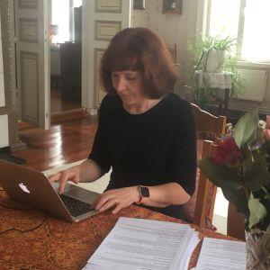 nainen kirjoittaa tietokoneella pöydän ääressä