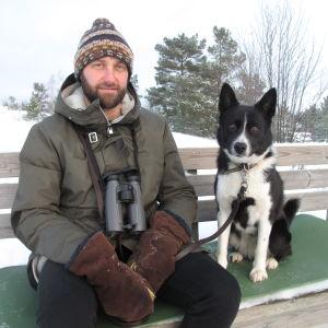 Man och hund sitter på bänk