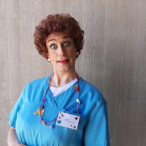 """Christoffer Strandberg återuppstår som """"Riitta"""" i Sjundeå. Sjuksköterska i turkos uniform."""