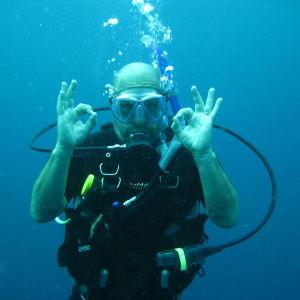 Jussi Pakkasvirta sukuletamassa kirkkaansinisessä vedessä, katsoo kohti kameraa ja näyttää käsimerkein, että kaikki on OK.