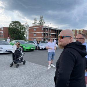 Ihmisiä ja Tesla-merkkisiä autoja Suonenjoen Teboilin pihassa.
