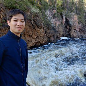 Japanilainen Kento seisoo kosken vieressä Kuusamossa.