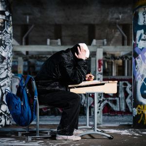 En person sitter hukad över en pulpet.
