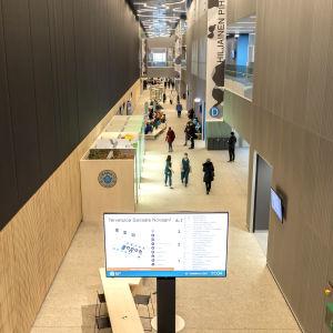 Människor går i aulan i Mellersta Finlands centralsjukhus.