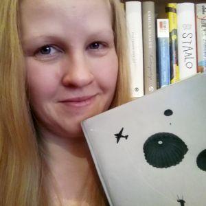 Satu Ekoluoma pitelee kädessään kirjaa kirjahyllyn edessä
