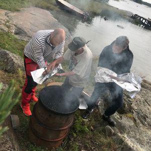 Ove Englund, Matias Jungar och Michael Björklund står och plockar ut fisk ur en rökugn.