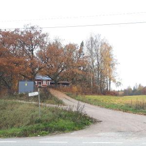 Ett rött hus skymtar bland höstgula träd.