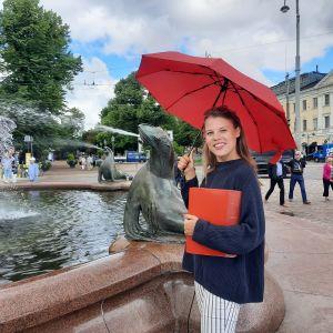 Maria Aho står med ett rött paraply.
