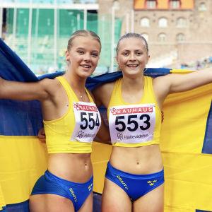 Nora Lindahl (t.h.) och Ella Borg (t.v.) poserar på Stockholms stadion draperad i den svenska flaggan.