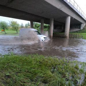 En vit minivan kör genom djupt flödvatten under en bro.