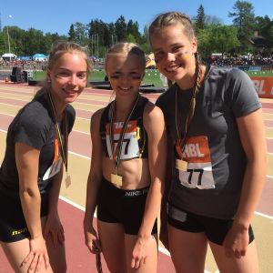 Tre flickor från S:t Olofsskolan med medaljer runt halsen under Stafettkarnevalen.