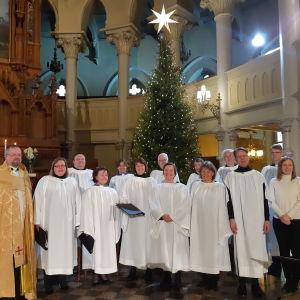 Celebrant Mikael Busck-Nielsen i ljusgul korkåpa tillsammans med Medarbetarkören klädda i vitt i Johanneskyrkan. I bakgrunden altare och julgran.
