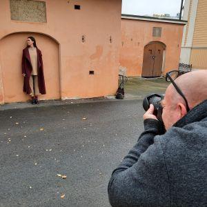 En fotograf tar foto på en kvinna som poserar med en jacka