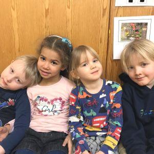 Fyra dagisbarn sitter tätt tillsammans.