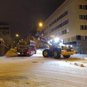 Lunta poistetaan kadun varresta Kuopiossa aamuyöllä.