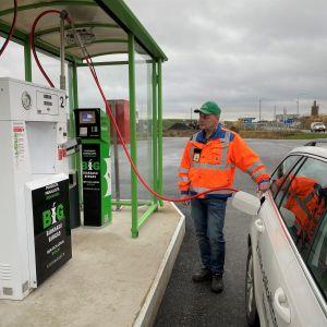 Man i orange jacka tankar en biogasbil.
