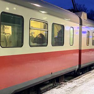 Ulkoa kuvattu matkustaja junassa maski kasvoillaan.