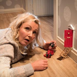 Maria Månsson (Mari Perankoski) makaa vatsallaan lattialla ja puuhastalee tonttuovella.