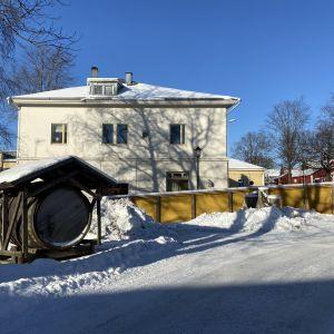 En gammal tunna står utställd på en innergård. Området är omgärdat med staket. I bakgrunden syns en äldre byggnad.