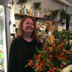 Kuvassa kukkakauppias Mari Havia liikkeessään kukkien keskellä.