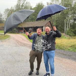 Två personer som står ute i regnet.