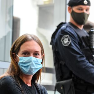 En kvinna med blå munskydd. I bakgrunden en polisman.