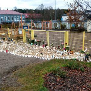 massor av gravljus, kramdjur och blommor framför lekparken i lyceiparken.