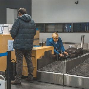 Matkalaukku hihnalle lentoasemalla.