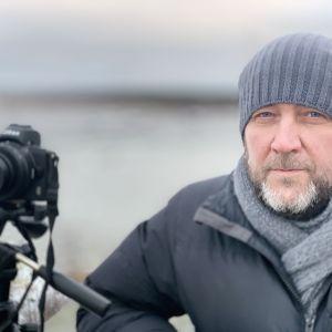 En man i vinterkläder står intill sin uppriggade kamera
