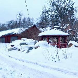 En snöig väg, stenhögar täckta av snö, gamla röda byggnader, en röd paviljong.