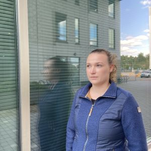 En kvinna står framför ett fönster. Hennes profil syns i bilden. Hon titta ut ur bilden och ser allvarlig ut.