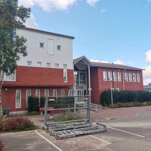En byggnad i rött och vitt tegel som är Sjundeå kommunhus.
