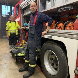 Kaksi miestä seisoo paloauton edessä hallissa.