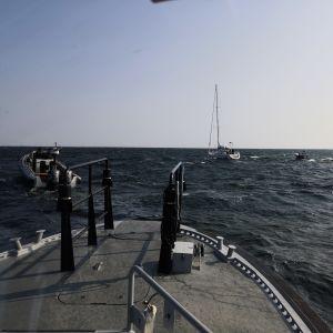 I mitten en segelbåt och runtomkring några motorbåtar.