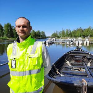 En man i gul väst står i solen på en brygga vid en träbåt