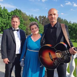 Juhlapukuinen pariskunta poseeraa muusikko Juha Tapion kanssa kesämaisemassa