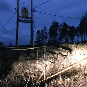 På bilden syns en transformator uppe mellan några stolpar. Framför transformatorn har man satt ut varningsband.