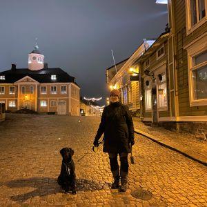 Barbro står på rådhustorget i Borgå med sin svarta hund.