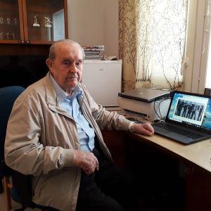 99-åriga Ragnar Nordström sitter vid skrivbordet med datorn öppen.