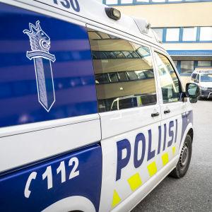 Närbild av polisens skåpbil i vitt och blått och en annan likadan bil syns i bakgrunden