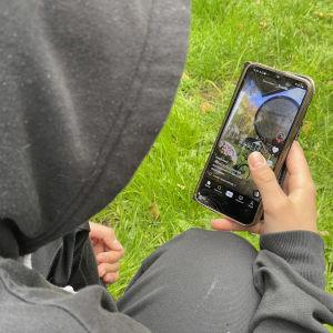Nuori selaa kännykästään TikTokin videoita