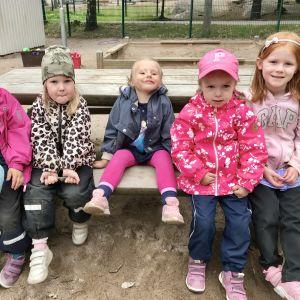 Fem flickor sitter på en bänk utomhus.