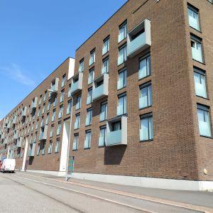 Hus i flera våningar, några balkonger, blå himmel.