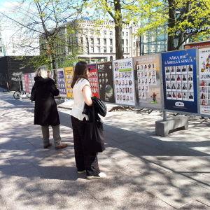 Personer ser på valreklami Helsingfors.
