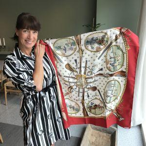 Malin Sveholm håller upp en står sidenscarf från modehuset Hermés.