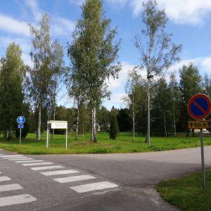 Korsning mellan väg och gång- och cykelväg. I bakgrunden gräsplan med träd.