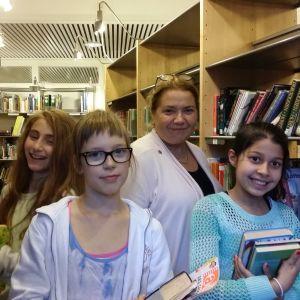 Opettaja ja oppilaita koulun kirjastossa.