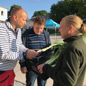 Mats Nyman ger en låda med fänkål till Matias Jungar och Michael Björklund.