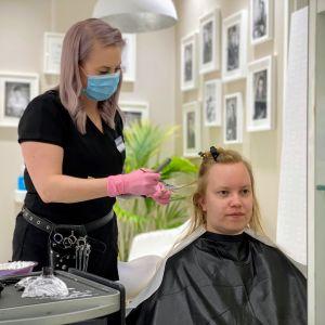 Kampaaja Lea Saari värjää Mari Huuskon hiuksia oululaisessa kampaamossa.